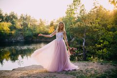 Beautiful bride stands with a bouquet in hands on a nature background stock photography