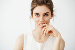 Portrait of young beautiful brunette girl looking at camera posing touching face over white background. Royalty Free Stock Images