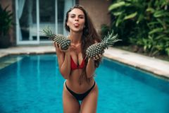 Portrait of young beautiful brunette girl in swimsuit with pineapple in her hands fruit holding on the breast. Sexy. Model with cute smile, posing near swimming Stock Photography