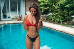 Portrait of young beautiful brunette girl in swimsuit with pineapple in her hands fruit holding on the breast. Sexy. Model with cute smile, posing near swimming Royalty Free Stock Photography