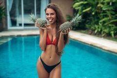 Portrait of young beautiful brunette girl in swimsuit with pineapple in her hands fruit holding on the breast. Sexy. Model with cute smile, posing near swimming Stock Photo