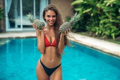 Portrait of young beautiful brunette girl in swimsuit with pineapple in her hands fruit holding on the breast. Model with cute smile, posing near swimming pool royalty free stock image