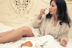 Portrait of a young beautiful brunette having breakfast Stock Image