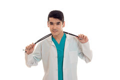 Portrait of young beautiful brunette man doctor in white uniform with stethoscope looking at the camera isolated on Royalty Free Stock Photos