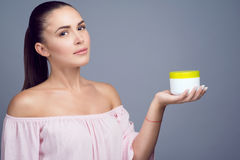 Portrait of young beautiful brunette with ponytail holding cosmetic jar on her palm and smiling. Stock Images