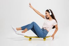 Portrait of young beautiful brunette in white headphone having f. Un on yellow skateboard, isolated over white background Royalty Free Stock Photography