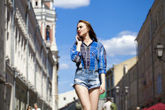 Portrait of young beautiful brunette woman in blue jeans short Stock Image