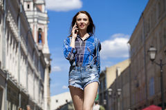 Portrait of young beautiful brunette woman in blue jeans short Stock Photography