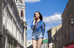 Portrait of young beautiful brunette woman in blue jeans short Royalty Free Stock Images