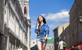 Portrait of young beautiful brunette woman in blue jeans short Stock Images
