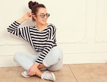 Girl with no makeup in summer hipster clothes posing near wall. Portrait of young beautiful brunette woman girl model with nude makeup in summer hipster clothes Royalty Free Stock Photography