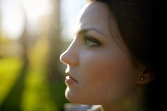 Portrait of young beautiful brunette woman in park.  Royalty Free Stock Images