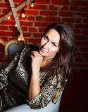 Portrait of young beautiful brunette woman sitting in chair as a Royalty Free Stock Photo