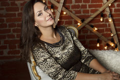 Portrait of young beautiful brunette woman sitting in chair as a Royalty Free Stock Image