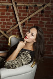 Portrait of young beautiful brunette woman sitting in chair as a royalty free stock images