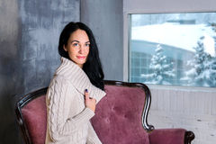 Portrait of young beautiful brunette woman. Winter wiew in window Royalty Free Stock Photography