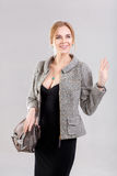 Portrait of young beautiful business woman blonde in black dress and with bag on gray background Stock Image