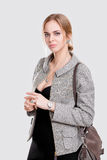 Portrait of young beautiful business woman blonde in black dress and with bag on gray background Royalty Free Stock Photos