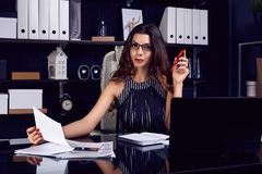 Young beautiful business woman working at stylish black desk. Portrait of young beautiful business woman in fashion suit and glasses working at stylish black royalty free stock images