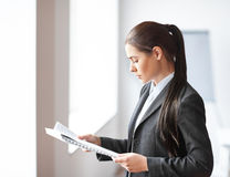 Portrait of young beautiful business woman reading documents in Stock Photo