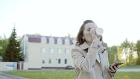 Portrait of a young beautiful business woman student walking around the city, drinking coffee, talking on the phone. Concept: new business, communication stock video footage