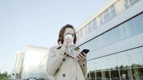 Portrait of a young beautiful business woman student walking around the city, drinking coffee, talking on the phone. Concept: new business, communication stock footage