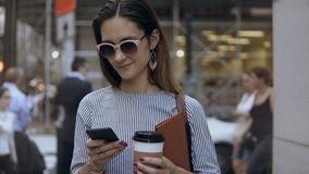 Portrait of young beautiful businesswoman with coffee cup and documents on crowded street using the smartphone. Busy female typing on mobile phone, using as stock video
