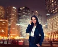 Young businesswoman, night cityscape on background. Portrait of young, beautiful businesswoman in glasses and suit with laptop in hands, night cityscape on Royalty Free Stock Photo