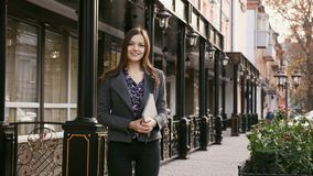 Portrait of young beautiful businesswoman looking at camera with smile outdoors, in the hands holding a tablet, slow