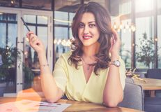 Portrait of young beautiful businesswoman sitting at table in restaurant. Stock Photo