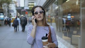 Portrait of young beautiful businesswoman in sunglasses talking on mobile phone and drinking coffee in downtown.