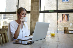 Portrait of a young beautiful businesswomen enjoying coffee during work on portable laptop computer Royalty Free Stock Photography