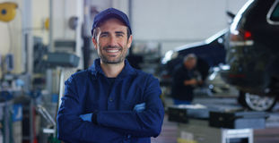 Portrait of a young beautiful car mechanic in a car workshop, in the background of service. Concept: repair of machines, fault dia. Gnosis, repair specialist Royalty Free Stock Photo