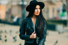 Portrait of young beautiful casual girl in jacket an black hat walking on  spring city street. Royalty Free Stock Image