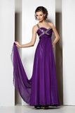 Young beautiful brunette in purple dress on white Stock Images
