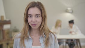 Portrait of young beautiful Caucasian girl with grey eyes looking at camera and smiling. Pretty European lady with stock video