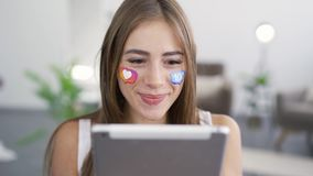 Portrait of young beautiful caucasian woman with painted social media icons on her face holding the tablet in hands and. Smiling. Addiction to gadgets and stock footage