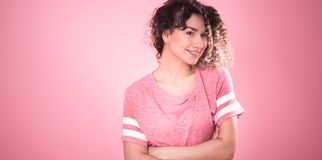 Portrait of a beautiful cheerful girl with curly hair on a pink background stock photography