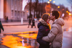 Portrait of young beautiful couple kissing in an autumn rainy day. Stock Image