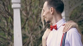 Portrait, young beautiful couple newlyweds hugging, the bride straightens the red bow tie on her fiance. looking at each stock video footage