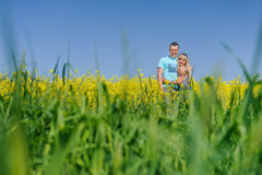 Portrait of young beautiful couple in rape field. Stunning sensual young couple in love posing in summer field, happy lifestyle concept. Man and Woman in love Royalty Free Stock Photos