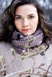 Portrait of a young beautiful curly brunette in beige coat Royalty Free Stock Photography