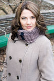 Portrait of a young beautiful curly brunette in beige coat Stock Photography