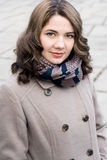 Portrait of a young beautiful curly brunette in beige coat Stock Photo