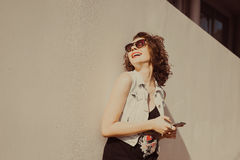 Portrait of young beautiful curly brunette girl in sunglasses with red lips talking phone does selfi Royalty Free Stock Photography