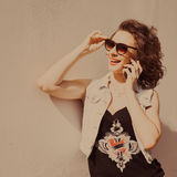 Portrait of young beautiful curly brunette girl in sunglasses with red lips talking phone does selfi. Close-up portrait of young beautiful curly brunette girl in Royalty Free Stock Photography