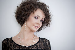 Portrait of a young beautiful curly brunette. Studio shot of a beautiful young woman with curly hair royalty free stock photo