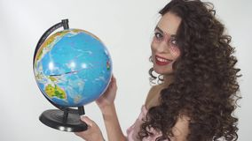 Portrait young beautiful curly girl with creative make up twisting globe with fun and pretty smile. Girl stops the globe stock video