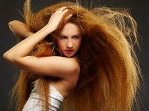 Long-haired curly redhead woman Stock Photo