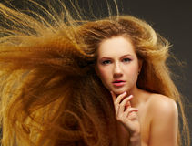 Long-haired curly redhead woman Stock Image